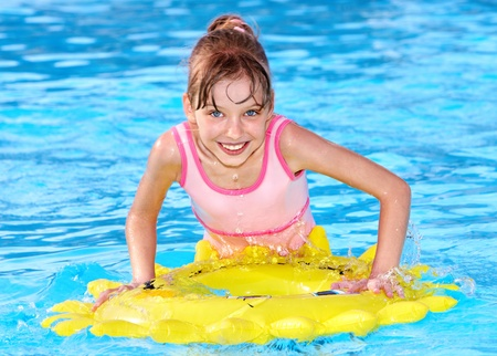 little girl swimsuit: Child sitting on inflatable ring in swimming pool.