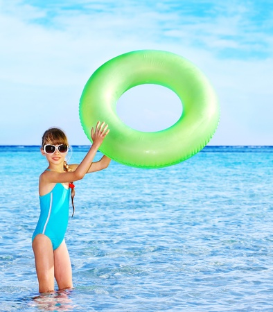 little girl swimsuit: Children holding inflatable ring in sea. Stock Photo