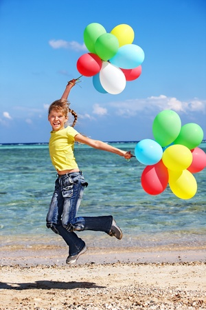 Child playing with balloons at the beach. photo