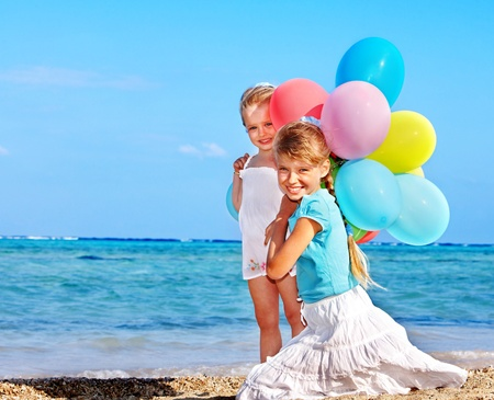 Children  playing with balloons at the beach. Stock Photo