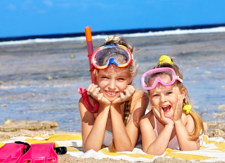 scuba goggles: Children playing on  beach. Snorkeling.