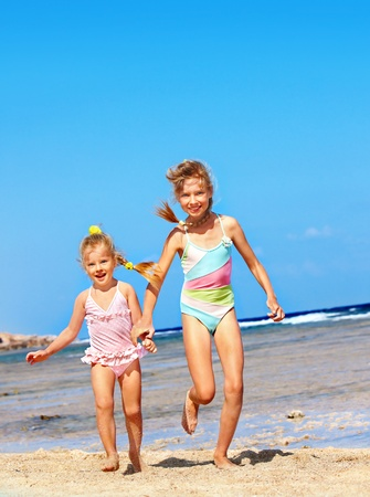 one piece swimsuit: Children holding hands running on  beach.