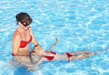 Swimming Instructor learn little girl swim. photo
