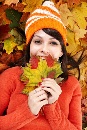 black sweater: Young woman in autumn orange leaves. Outdoor.