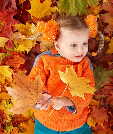 Little girl in autumn orange leaves. Outdoor. Stock Photo - 9898542