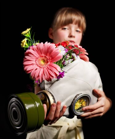 Little girl holding flowers and gas mask . Stock Photo - 9897982