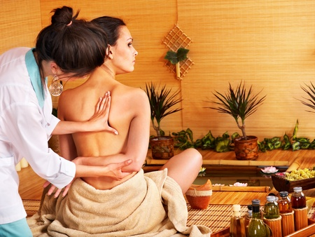Massage therapy: Young woman getting massage in bamboo spa..
