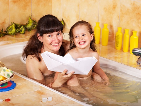 Mother and child washing in bubble bath . photo