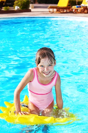 one piece: Child sitting on inflatable ring in swimming pool.