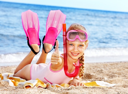 scuba goggles: Thumb up of child playing on beach.