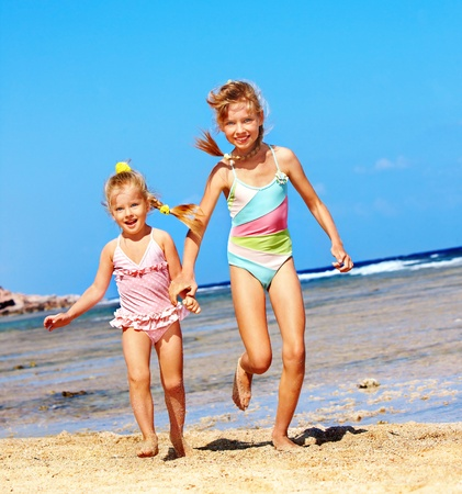 Children holding hands running on  beach.  photo