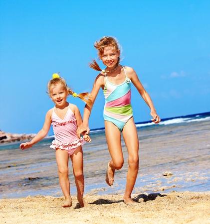 ni�os caminando: Ni�os de la mano corriendo en la playa. Foto de archivo