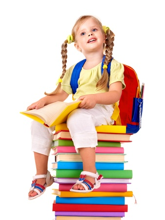 Little girl sitting on pile of books. Isolated. photo