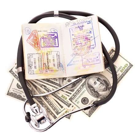health care concept: Medical still life with stethoscope, money and passport. Isolated. Stock Photo