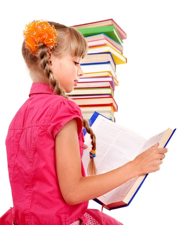 Little girl reading open  book on table. Isolated. photo