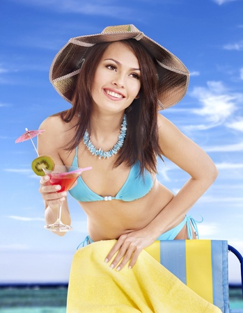 Girl in bikini drink juice on beach. Stock Photo - 9899355