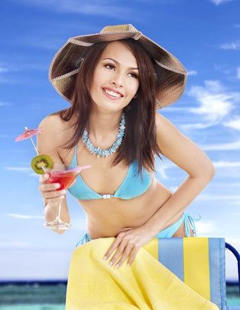 Girl in bikini drink juice on beach. photo