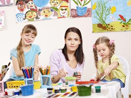 Child painting in preschool. Teacher help by little\ girl.