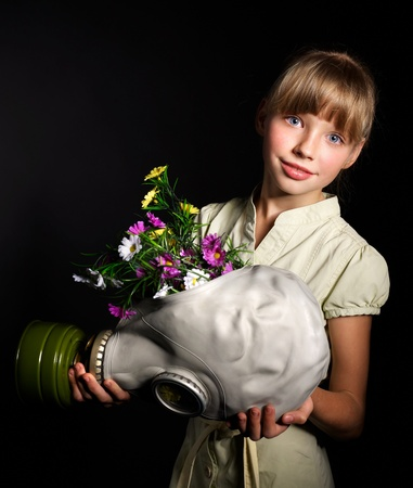 Little girl holding flowers and gas mask . Stock Photo - 9899354