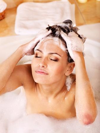 baarse: Mujer lav�ndose el pelo en el ba�o de burbujas.