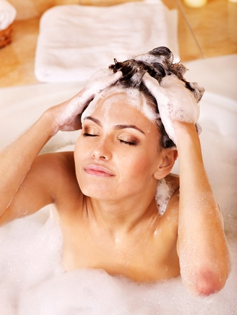 Woman washing hair in bubble bath. photo