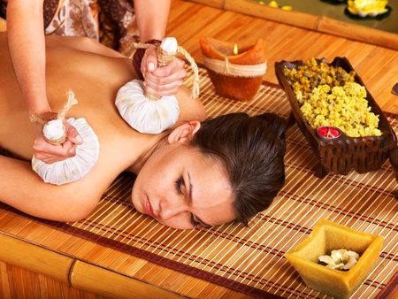 thai massage: Young woman getting massage in bamboo spa.