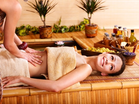 beauty therapist: Young woman getting massage in bamboo spa.