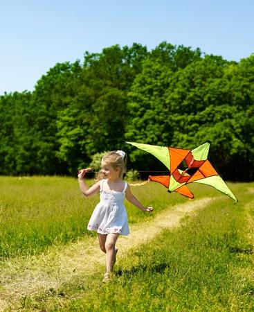 flying kite: Child flying kite outdoor. little girl running across  green grass.