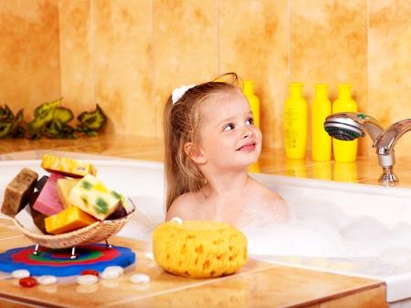 Child washing in bubble bath . photo