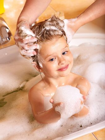 steam bath: Child washing hair in bubble bath.