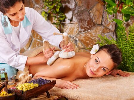 herbal massage ball: Woman getting thai herbal compress massage in spa.