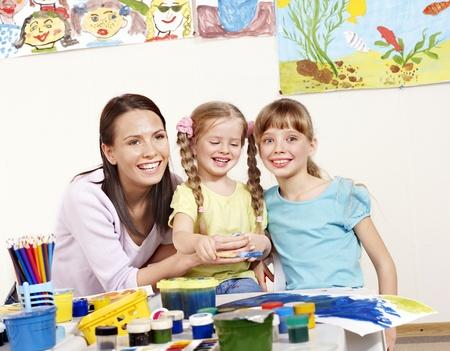 maestra preescolar: Ni�o pintura en preescolar. Ayuda de profesor por la ni�a. Foto de archivo