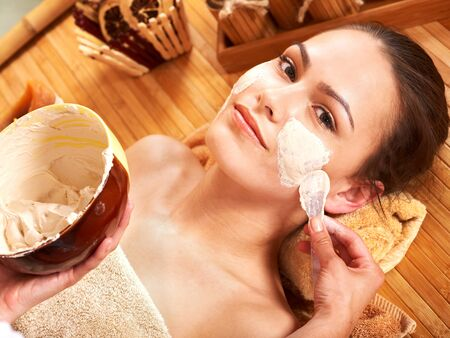 beauty parlour: Beautiful girl having clay facial mask apply by beautician. Stock Photo