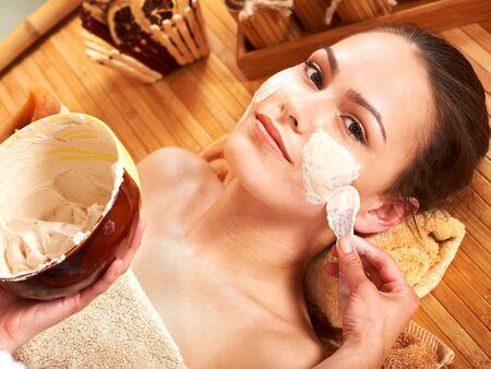 parlour: Beautiful girl having clay facial mask apply by beautician. Stock Photo