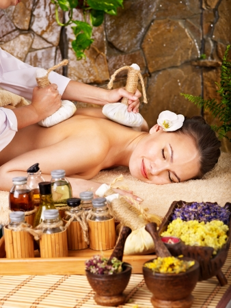 Woman getting thai herbal compress massage in spa. Stock Photo - 9972570