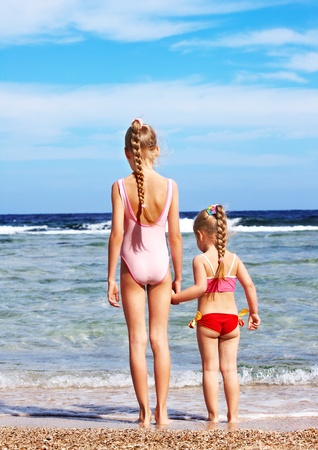 child swimsuit: Children holding hands walking on the beach. Rear view.