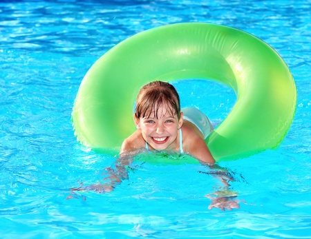 little girl smiling: Children sitting on inflatable ring in swimming pool. Stock Photo