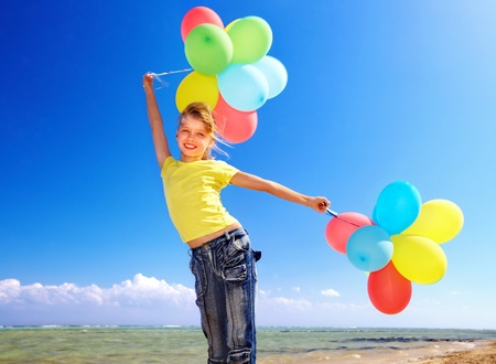 Child playing with balloons at the beach. Stock Photo - 10224969