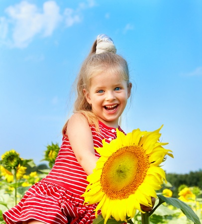 Child holding sunflower outdoor. photo