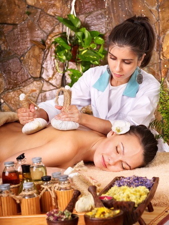 Woman getting thai herbal compress massage in spa. photo