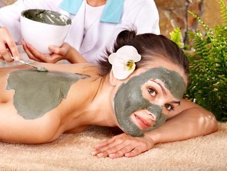 Beautiful girl having clay body mask apply by beautician. photo