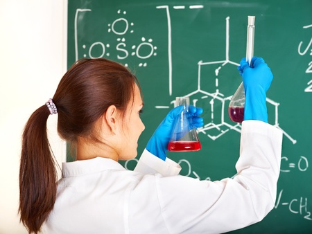 experiment: Female chemistry student with flask in classroom. Stock Photo