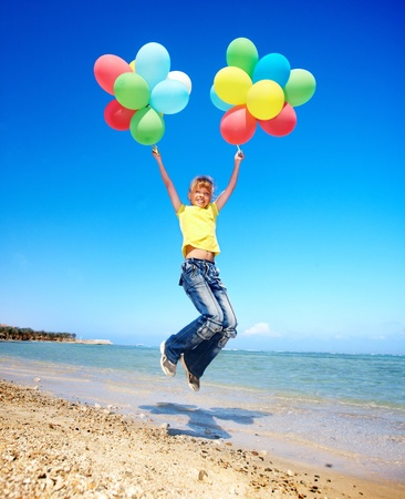 blue jeans kids: little girl playing with balloons at the beach. Stock Photo