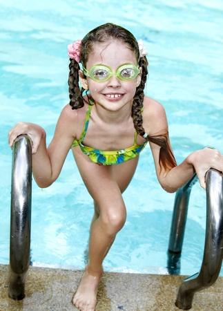 Little girl swim  in swimming pool. photo