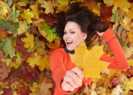 Young woman in autumn orange leaves. Outdoor. Stock Photo - 10292544