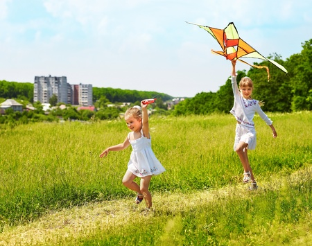 woman flying: Group children flying kite outdoor.