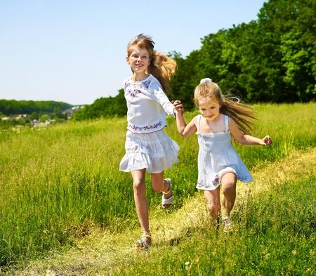 Group children running across green grass outdoor.