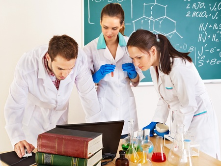 laboratory equipment: Group chemistry student with flask in classroom.