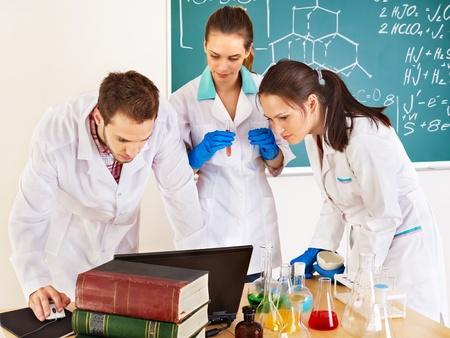 examenes de laboratorio: Grupo de estudiantes de química con frasco en el aula. Foto de archivo
