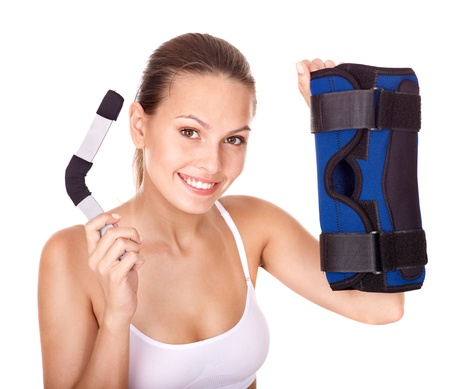 knee bend: Happy girl holding hinged knee braces. Isolated.